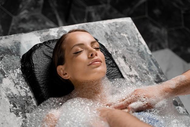 Ritratto del primo piano della ragazza sulle procedure di peeling della schiuma nella spa. la modella si sta rilassando nell'hammam turco.