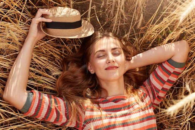 Close up ritratto di ragazza che riposa nel campo di fattoria, in posa con gli occhi chiusi, tenendo in mano il cappello di paglia, indossando la camicia a righe, sembra calmo e felice, donna posa sul terreno circondato da spighette.