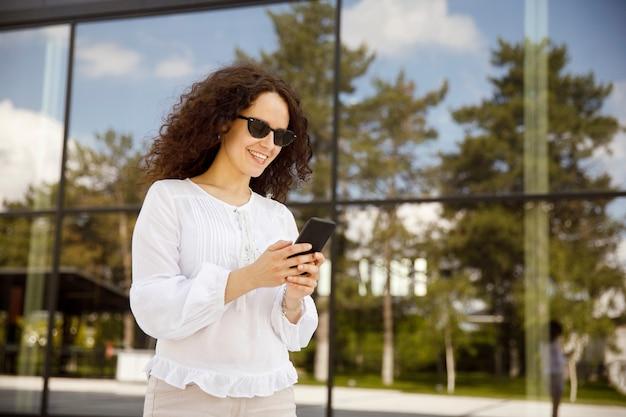 Ritratto del primo piano di una ragazza con i capelli ricci, guardando il cellulare, contro un edificio con sfondo della finestra.