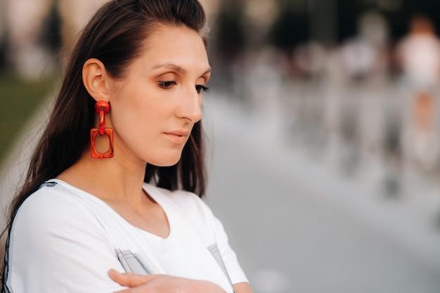 Ritratto del primo piano di una ragazza con orecchini rossi in abiti bianchi in città.