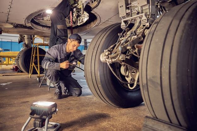 Ritratto ravvicinato dell'equipaggio di terra che lavora all'aeroporto mentre ripara gli aeroplani e controlla il carrello di atterraggio