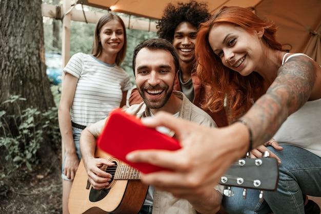 Ritratto ravvicinato di un gruppo di giovani amici che vanno in giro viaggiando insieme nel glamping nella foresta divertendosi a suonare la chitarra, facendo selfie, in streaming sui social media seduti in tenda ridendo