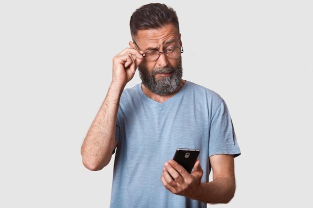 Primo piano ritratto di ragazzo vestito grigio maglietta casual, tenendo il telefono, legge qualcosa con attenzione, alza gli occhiali per vedere meglio