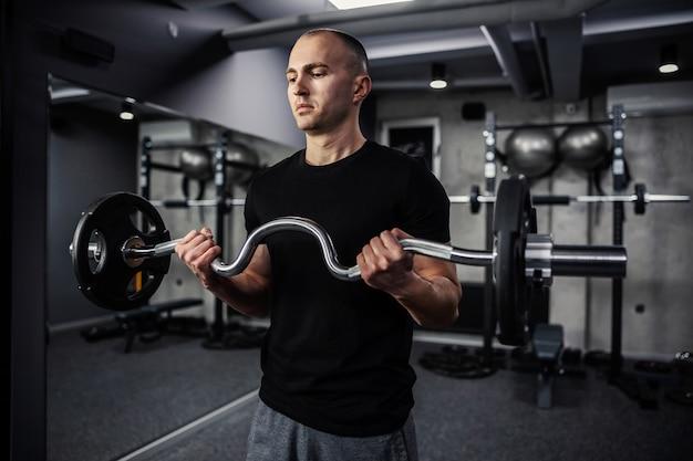 Un ritratto ravvicinato di metà del corpo di un uomo sportivo e muscoloso in palestra che esercita i suoi bicipiti con i pesi