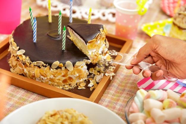 Close up ritratto di mano per affettare la torta al cioccolato sul set da tavola per la festa del bambino