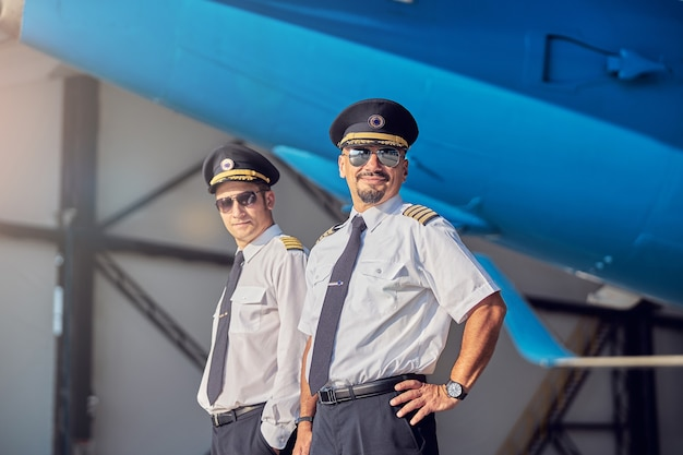 Ritratto ravvicinato di bei maschi fiduciosi in camicia bianca e cappelli da pilota che guardano la macchina fotografica vicino all'aereo