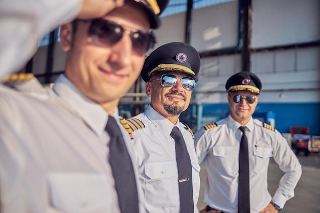Primo piano ritratto di bei piloti fiduciosi in camicia bianca e occhiali da sole in posa e guardando la macchina fotografica mentre si trova all'hangar dell'aeroporto