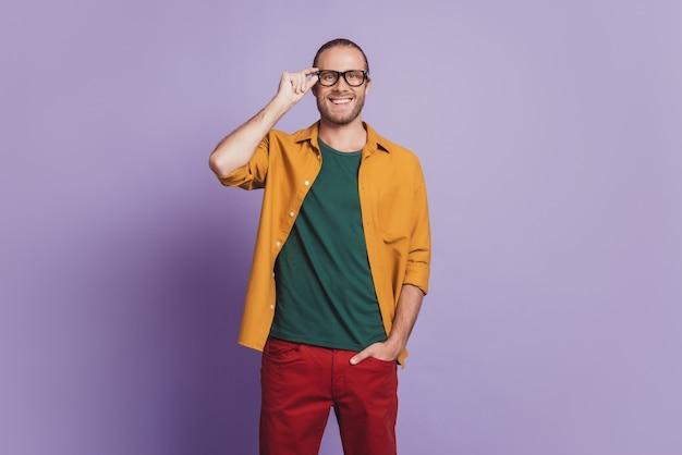 Ritratto ravvicinato di un bel ragazzo positivo con le dita degli occhiali sul muro viola