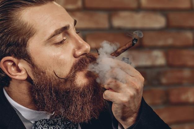 Chiuda sul ritratto di un bell'uomo bello con i baffi e la barba che fuma un sigaro marrone su uno sfondo di muro di mattoni. concetto di sigaro