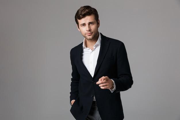 Close up ritratto di un bel giovane imprenditore vestito in tuta isolato sopra il muro grigio, puntare il dito
