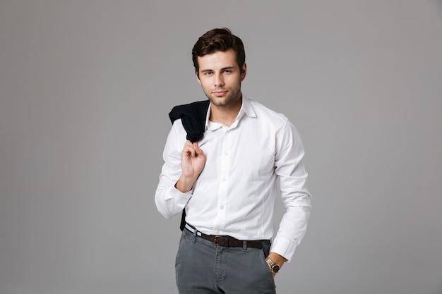 Close up ritratto di un bel giovane imprenditore in piedi isolato su un muro grigio, tenendo in mano una giacca