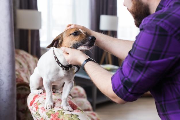 Close up ritratto bel giovane hipster uomo gioca e ama il suo buon amico cane a casa. emozioni umane positive, espressione facciale, sentimenti.