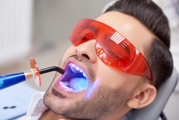Close up ritratto di un bel giovane che indossa occhiali protettivi ottenendo riempimento dei denti fatto presso la clinica dentale professionalità sicurezza sanitaria medicina sorriso trattamento odontoiatria.