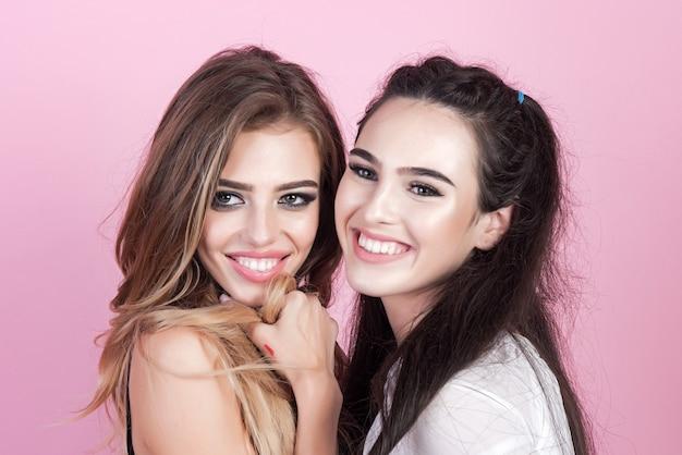 Chiuda sul ritratto delle donne sorridenti degli amici felici affrontano il trucco naturale di modo e di bellezza