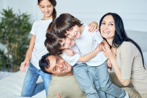 Primo piano ritratto di felice famiglia latina, genitori e bambini che sorridono alla telecamera mentre si divertono insieme a casa. infanzia felice, concetto di genitorialità