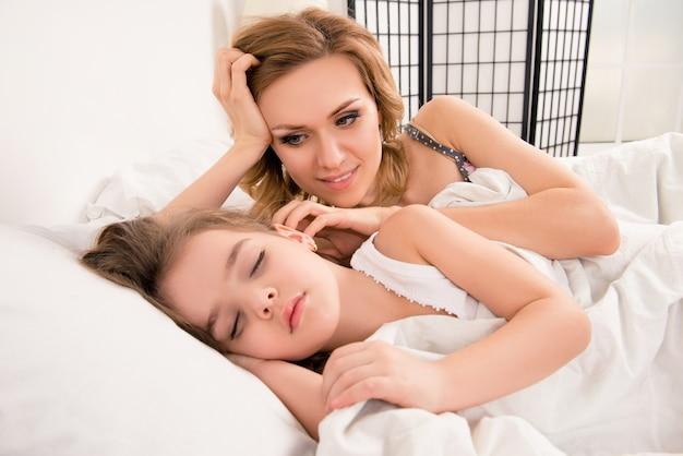 Chiuda sul ritratto della madre felice e del suo bambino che dorme nel letto