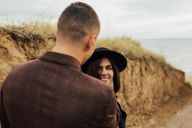 Chiuda sul ritratto della coppia sorridente felice nell'amore, ragazzo che abbraccia la sua ragazza in mare.