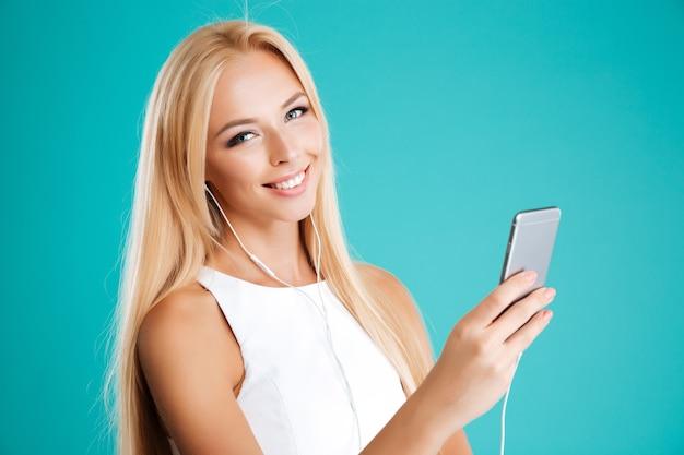 Chiuda sul ritratto di una ragazza sorridente felice con gli auricolari e il telefono cellulare isolato sulla parete blu