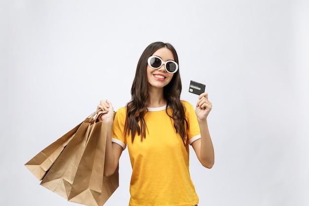 Ritratto del primo piano di giovane donna castana felice in occhiali da sole che tengono carta di credito e sacchetti della spesa variopinti