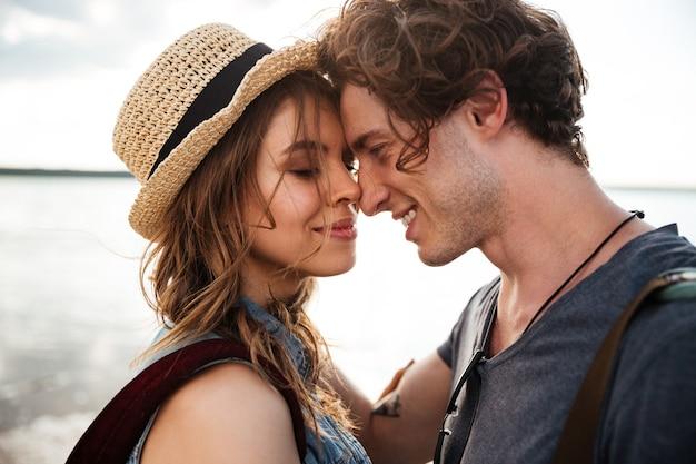 Close up ritratto di felice coppia giovane innamorato che si abbracciano sulla spiaggia