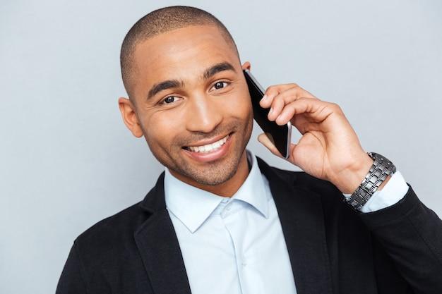 Ritratto ravvicinato di un giovane felice che parla al cellulare isolato