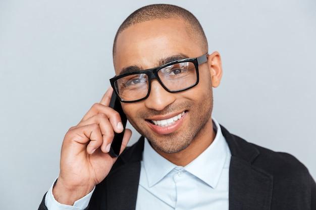 Ritratto ravvicinato di un giovane uomo felice che indossa occhiali che parla al cellulare isolato su sfondo grigio