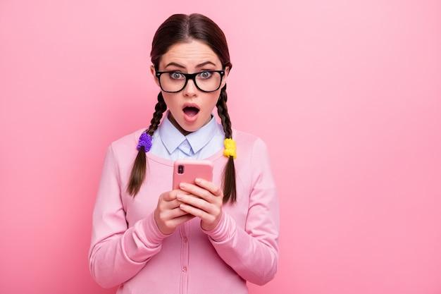 Ritratto ravvicinato di lei attraente piuttosto adorabile stupita stupita sbalordita ragazza geek utilizzando gadget digitale 5g app come antipatia condividi reazione repost isolata su sfondo rosa pastello