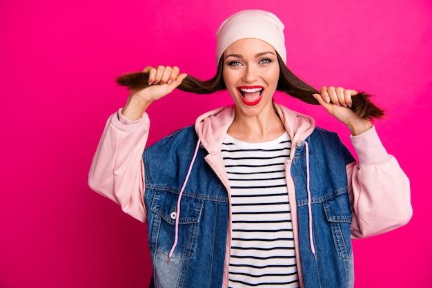 Ritratto del primo piano di lei bella ragazza funky allegra attraente divertendosi indossando street style holding facendo acconciatura code isolato sopra brillante vivido splendore vibrante colore rosa fucsia