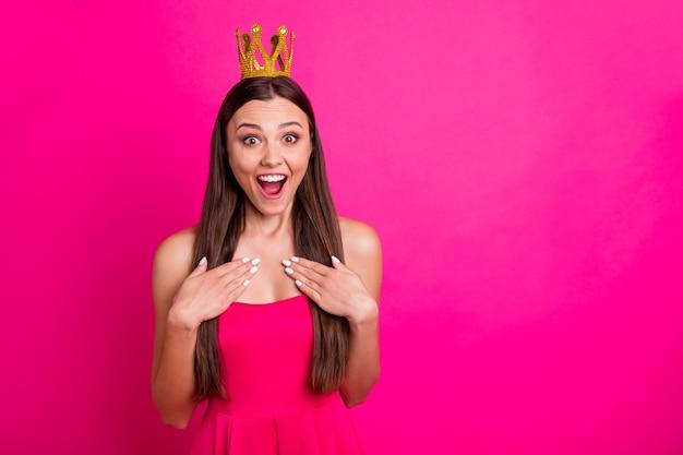 Ritratto del primo piano di lei bella ragazza dai capelli lunghi felice allegro allegro allegro che indossa la corona che esprime gioia grande notizia isolato su sfondo di colore rosa fucsia vibrante brillante vivido splendore