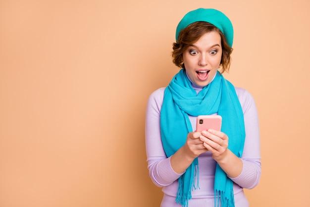 Ritratto ravvicinato di lei bella attraente bella stupita allegra allegra ragazza dipendente che utilizza la navigazione cellulare commento feedback multimediale multimediale isolato su sfondo beige color pastello