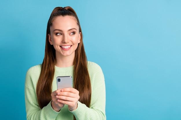 Close-up ritratto di lei bella attraente bella allegra allegra ragazza dai capelli castani utilizzando dispositivo guardando da parte copia spazio vuoto annuncio isolato luminoso vivido brillare vibrante sfondo di colore blu