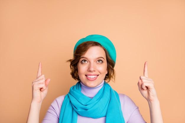 Close-up ritratto di lei bella attraente bella fiduciosa allegra ragazza allegra che punta l'indice su annuncio annuncio soluzione decisione nuova novità copia spazio isolato su sfondo beige color pastello