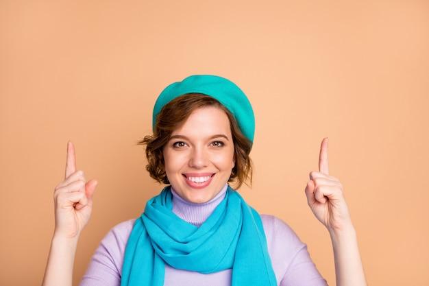 Close-up ritratto di lei bella attraente bella piuttosto affascinante allegra ragazza allegra che punta due dita in alto annuncio annuncio soluzione decisione nuova novità isolato su sfondo beige color pastello