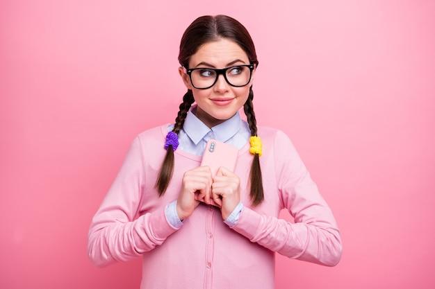 Ritratto del primo piano di lei bella attraente bella carina intelligente allegra sognante curiosa ragazza geek che tiene in mano abbracciando il dispositivo digitale isolato su sfondo rosa color pastello