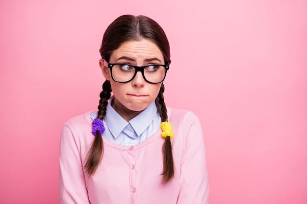 Ritratto ravvicinato di lei bella attraente piuttosto adorabile preoccupata timida intelligente intelligente ragazza geek indossando specifiche guardando da parte studio imparare istruzione isolato su sfondo rosa color pastello