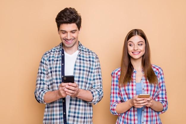 Ritratto del primo piano del suo lui lei lei bella coppia allegra allegra attraente che indossa la camicia a quadri utilizzando l'app 5g di marketing multimediale moderno isolato sopra priorità bassa di colore pastello beige