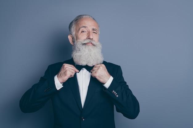Ritratto del primo piano del suo lui bello contenuto attraente orgoglioso arrogante uomo dai capelli grigi che indossa lo smoking che fissa la cravatta a farfalla che si prepara per l'evento isolato su sfondo di colore pastello viola viola grigio