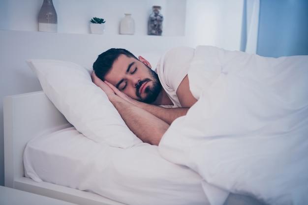 Ritratto del primo piano del suo ragazzo castana pacifico attraente bello che si trova sul letto bianco che riposa addormentato addormentato tempo di notte a tarda sera casa camera d'albergo appartamento al chiuso