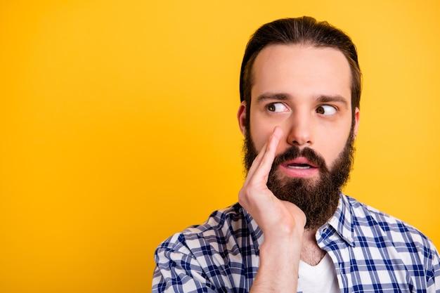 Ritratto del primo piano del suo ragazzo barbuto confuso preoccupato attraente bello in camicia a quadri che dice grande segreto