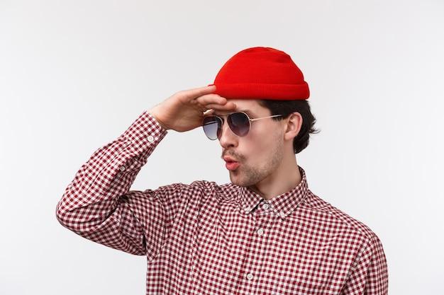 Ritratto di close-up di ragazzo giovane hipster incuriosito ed eccitato sotto mentite spoglie, occhiali da sole e berretto rosso, guardando in lontananza, vedere qualcosa di super cool lontano, stare stupito su un muro bianco