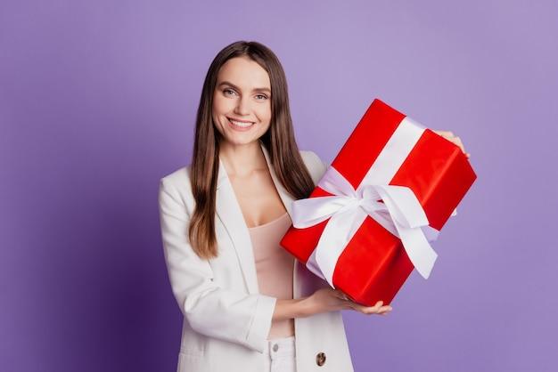 Close up ritratto di signora tenere scatola regalo sorriso a trentadue denti indossare abito formale in posa sul muro viola