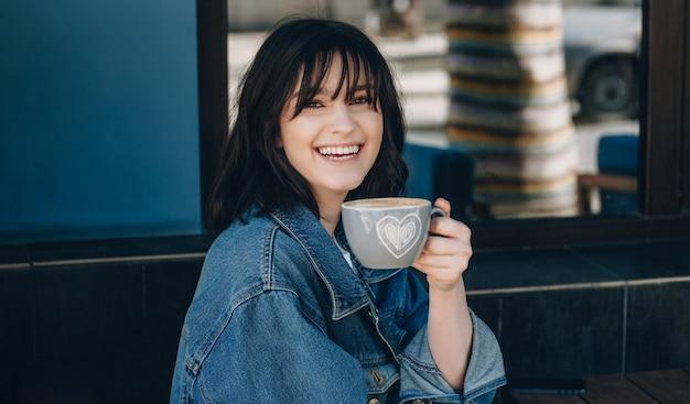 Close up ritratto di signora con i capelli neri sorridendo alla telecamera e bevendo una tazza di caffè