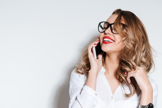 Ritratto ravvicinato di una donna che ride che parla al telefono isolata su un muro bianco