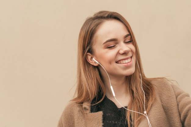 Ritratto del primo piano che ascolta la musica in sue cuffie con i suoi occhi chiusi e sorridenti, fondo beige della parete