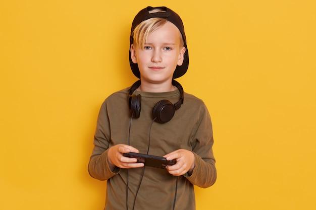 Close up ritratto di bambino bambino gioca con il suo telefono, mantiene le pietre intorno al collo, abiti camicia verde e cappello all'indietro. infanzia e concetto di tecnologia moderna.
