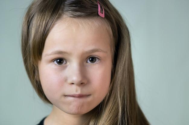Chiuda sul ritratto della ragazza del piccolo bambino con l'espressione divertente del fronte.