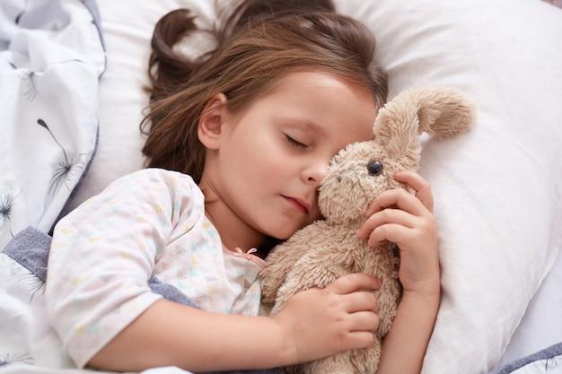 Chiuda sul ritratto della bambina che abbraccia il suo orsacchiotto e di essere felice, riposando dopo una giornata interessante in kinder garten