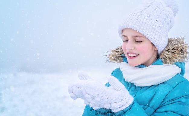 Ritratto del primo piano di una bambina che cattura i fiocchi di neve con le mani in guanti.