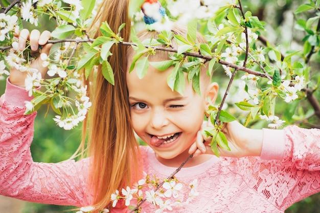 Chiuda sul ritratto della bambina che sbatte le palpebre in camicia rosa con i fiori
