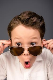 Chiuda sul ritratto del ragazzino scioccato in bicchieri con la bocca aperta